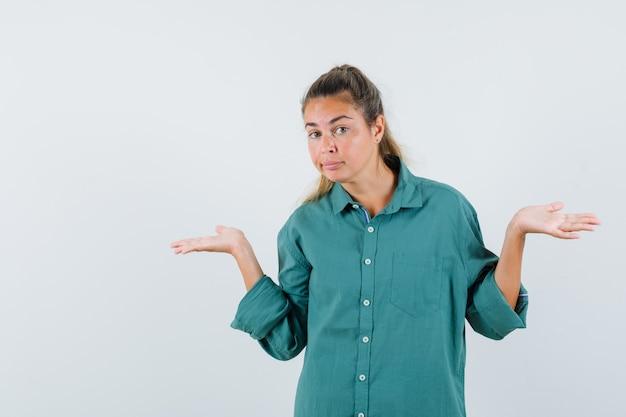 Jonge vrouw die hulpeloos gebaar in blauw overhemd toont en verward kijkt