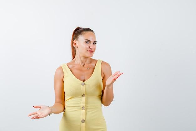 Jonge vrouw die hulpeloos gebaar in gele kleding toont en raadsel kijkt