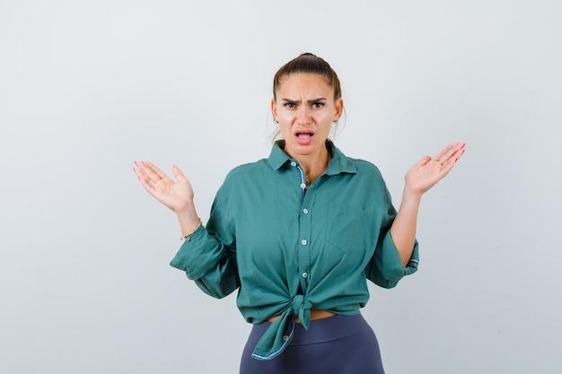 Jonge vrouw die hulpeloos gebaar in groen overhemd toont en verward kijkt. vooraanzicht.