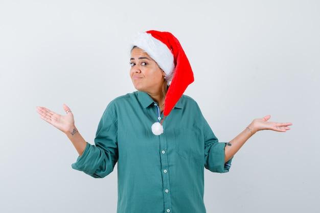 Jonge vrouw die hulpeloos gebaar in overhemd, kerstmuts toont en besluiteloos kijkt, vooraanzicht.