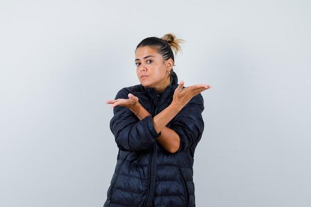 Jonge vrouw die hulpeloos gebaar in pufferjas toont en verward kijkt. vooraanzicht.