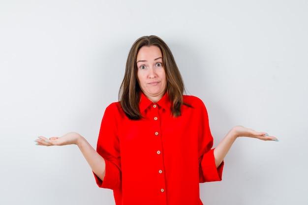 Jonge vrouw die hulpeloos gebaar in rode blouse toont en verward, vooraanzicht kijkt.