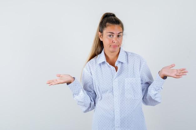 Jonge vrouw die hulpeloos gebaar in wit overhemd toont en verbaasd kijkt