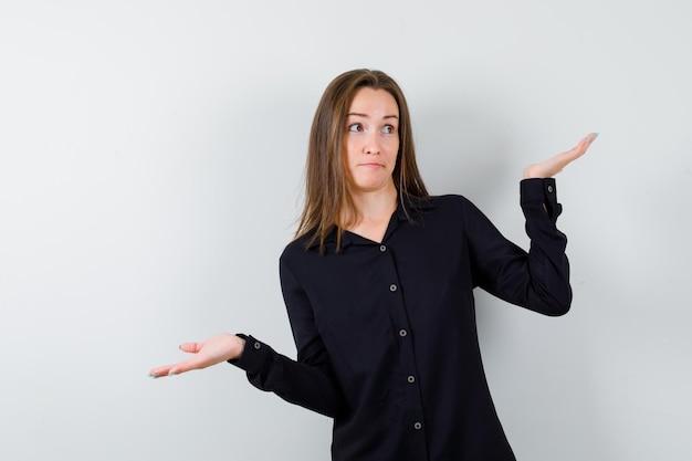 Jonge vrouw die hulpeloos gebaar toont en verbaasd kijkt