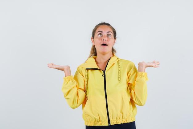 Jonge vrouw die hulpeloos gebaar toont terwijl het opzoeken in gele regenjas en verward kijkt