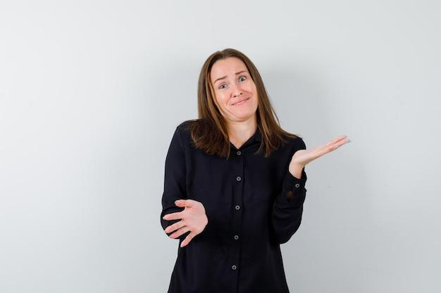 Jonge vrouw die hulpeloos gebaar toont