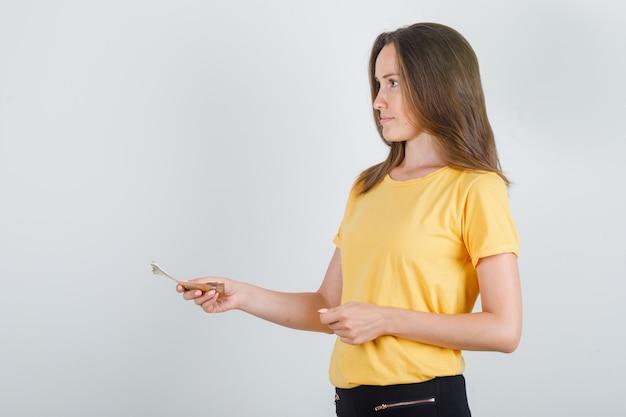 Jonge vrouw die iemand geld in gele t-shirt betaalt