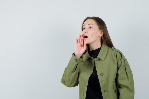 Jonge vrouw die iemand in groene jas roept en geconcentreerd kijkt. vooraanzicht. ruimte voor tekst