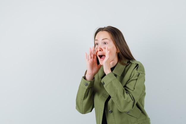 Jonge vrouw die iemand met luide stem in groene jas belt en geconcentreerd kijkt. vooraanzicht. ruimte voor tekst