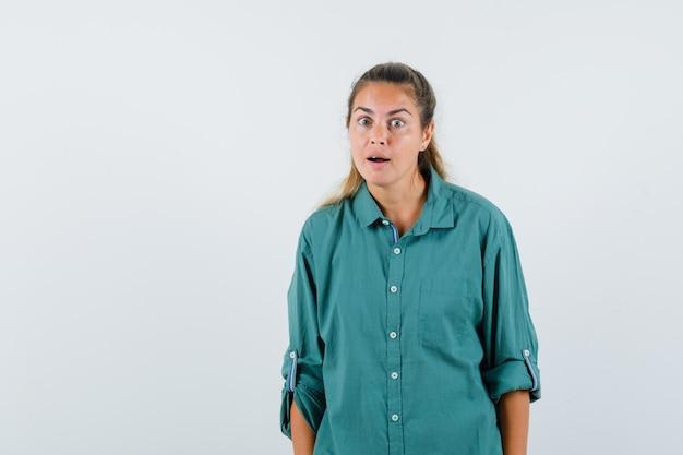 Jonge vrouw die iets in blauw overhemd hoort en geïnteresseerd kijkt
