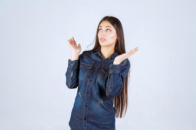 Jonge vrouw die iets in haar open hand toont