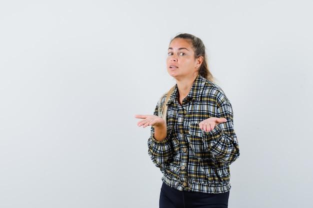 Jonge vrouw die iets in shirt, korte broek laat zien of iets aanbiedt en er zelfverzekerd uitziet. vooraanzicht.