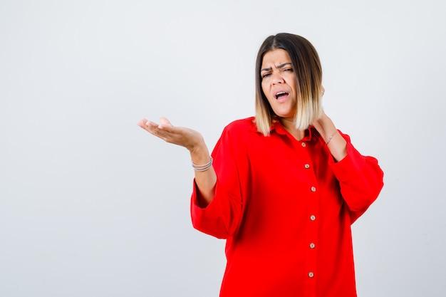 Jonge vrouw die iets laat zien terwijl ze de hand op de nek houdt in een rood oversized shirt en er ontevreden uitziet, vooraanzicht.