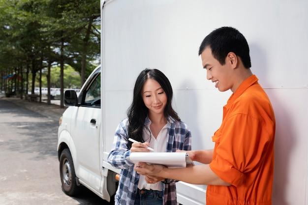 Jonge vrouw die iets op klembord naast de leveringsman ondertekent