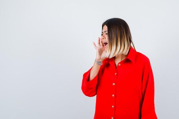 Jonge vrouw die iets schreeuwt in een rood oversized shirt en er serieus uitziet, vooraanzicht.