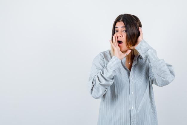 Jonge vrouw die iets schreeuwt terwijl ze de hand in de buurt van de mond houdt in een te groot shirt en er verbaasd uitziet. vooraanzicht.
