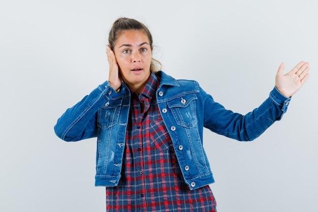 Jonge vrouw die iets toont, hand op oor in overhemd, jasje houdt en peinzend kijkt. vooraanzicht.