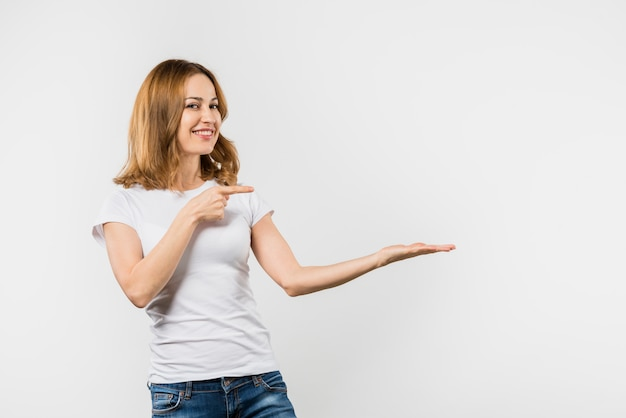 Jonge vrouw die iets voorstelt tegen witte achtergrond