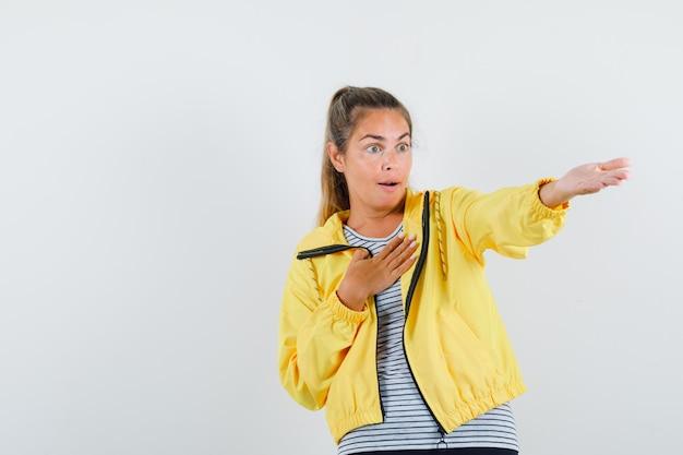 Jonge vrouw die iets weg laat zien in t-shirt, jasje en verbaasd kijkt. vooraanzicht.