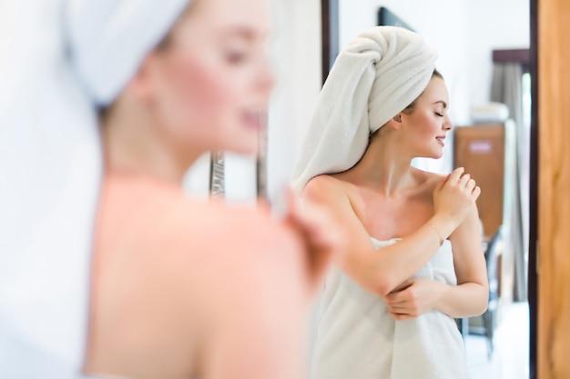 Jonge vrouw die in badjas in badkamerspiegel thuis kijkt