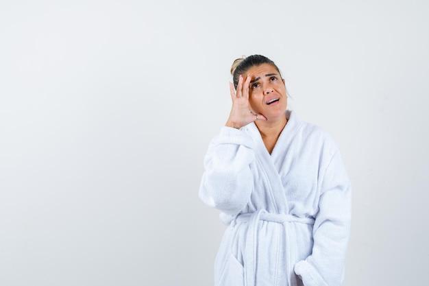 Jonge vrouw die in badjas omhoog kijkt en nadenkend kijkt