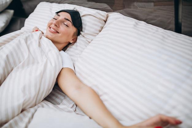 Jonge vrouw die in bed in de ochtend rust