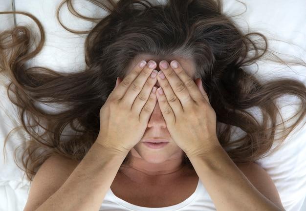 Jonge vrouw die in bed ligt en vermoeide vrouw die haar gezicht bedekt met handen kan niet slapen voelt zich uitgeput