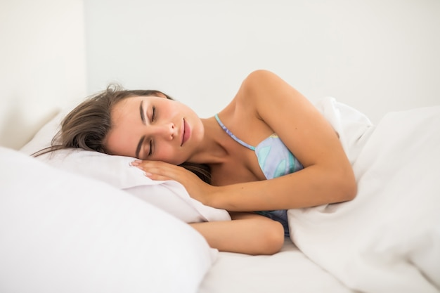 Jonge vrouw die in bed met handen naast haar hoofd op het hoofdkussen rust.