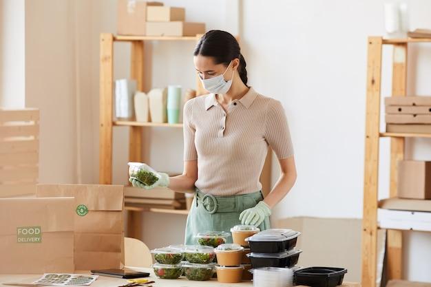 Jonge vrouw die in beschermend masker de dozen met voedsel inpakt die zij contactloze levering maakt