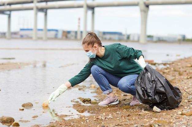 Jonge vrouw die in beschermend masker het vuilnis in de zak zet die zij de rivier van huisvuil schoonmaakt