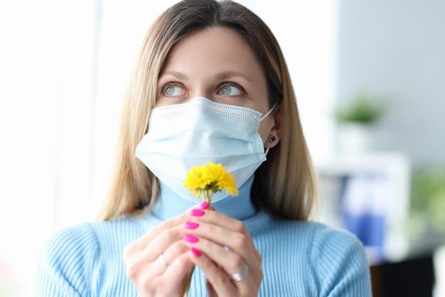 Jonge vrouw die in beschermend medisch masker gele bloem snuiven