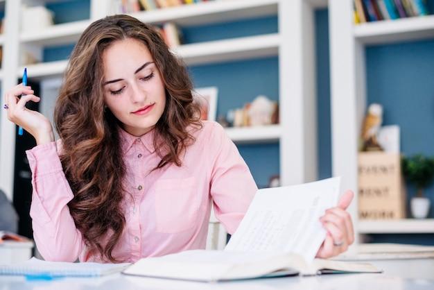 Jonge vrouw die in bibliotheek bestudeert