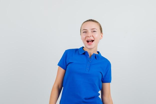 Jonge vrouw die in blauw en t-shirt gelukkig kijkt