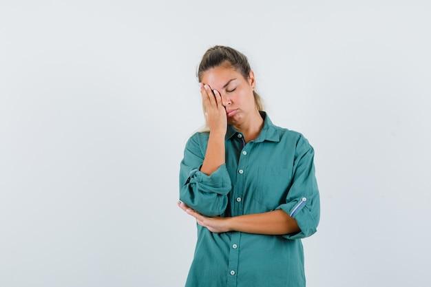 Jonge vrouw die in blauw overhemd aan haar hand leunt en slaperig kijkt
