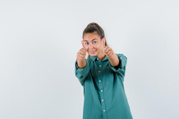 Jonge vrouw die in blauw overhemd duim toont en blij kijkt