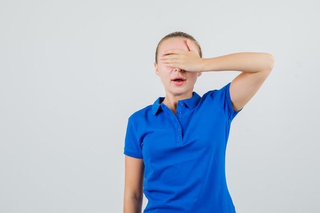 Jonge vrouw die in blauw t-shirt hand op ogen houdt en opgewekt kijkt
