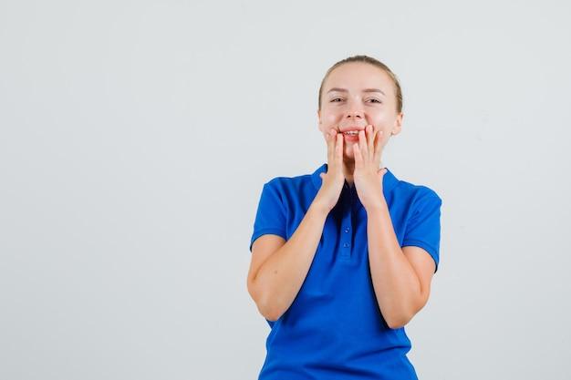 Jonge vrouw die in blauw t-shirt handen dichtbij mond houdt en gelukkig kijkt