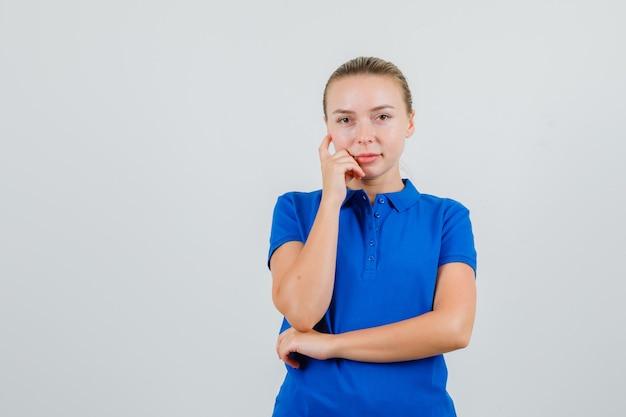 Jonge vrouw die in blauw t-shirt kijkt en verstandig kijkt