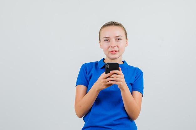 Jonge vrouw die in blauw t-shirt mobiele telefoon houdt en glimlacht
