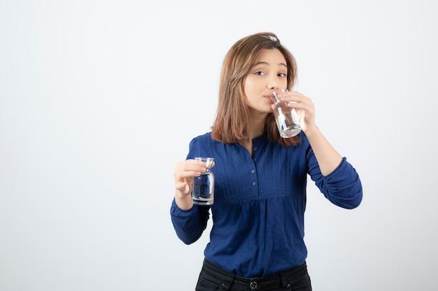 Jonge vrouw die in blauwe blouse glas water drinkt.