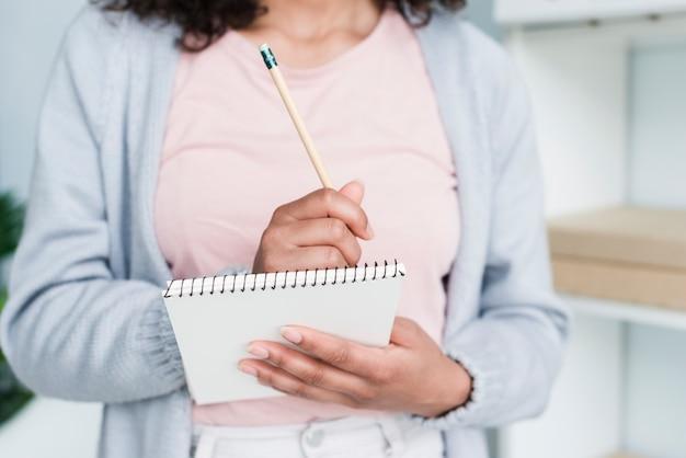 Jonge vrouw die in blocnote schrijft