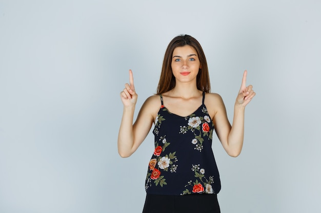 Jonge vrouw die in bloementop benadrukt en zelfverzekerd kijkt