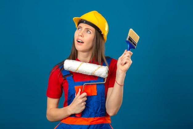Jonge vrouw die in bouw eenvormige en gele veiligheidshelm een de verfrol en borstel van de idee peinzende uitdrukking denken die zich op blauwe achtergrond bevinden