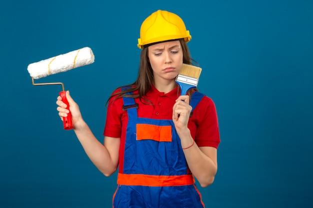 Jonge vrouw die in bouw eenvormige en gele veiligheidshelm met de ernstige de verfrol en borstel denken die van de gezichts peinzende uitdrukking zich op blauwe achtergrond bevinden