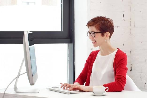 Jonge vrouw die in bureau werkt, bij bureau zit, computer met behulp van en op het scherm kijkt.