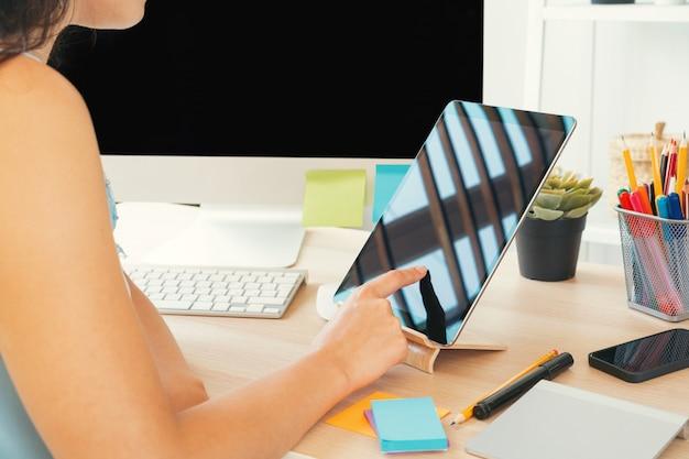 Jonge vrouw die in bureau werkt dat computer met behulp van, die bij bureau zit