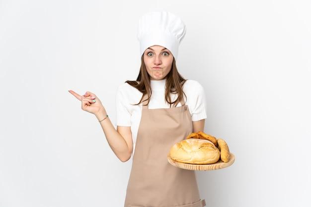 Jonge vrouw die in chef-kok eenvormig op witte muur aan de laterals richten die twijfels hebben