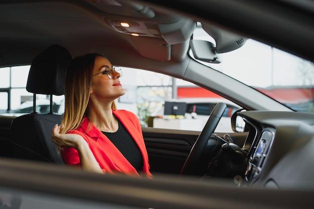 Jonge vrouw die in de achteruitkijkspiegel van een auto kijkt