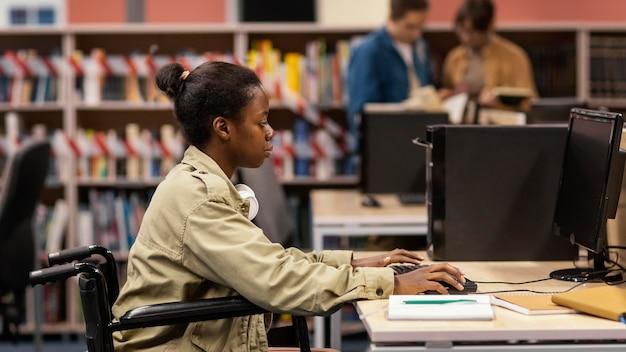 Jonge vrouw die in de bibliotheek studeert