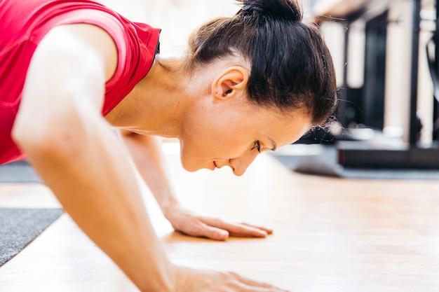 Jonge vrouw die in de gymnastiek uitwerkt